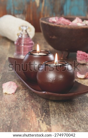 Spa still life. Spa concept with aromatherapy candles and red rose petals. Macro photograph with shallow depth of field. - stock photo