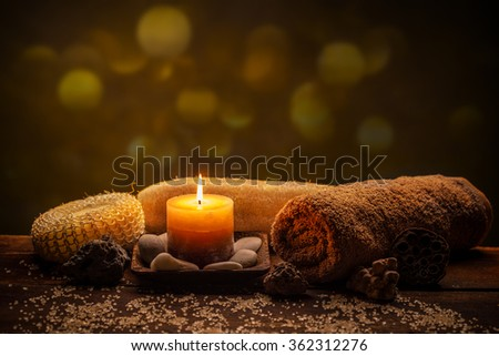 Spa still life with aromatic candle, stones and towel - stock photo