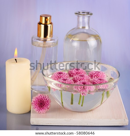 Spa still life with candle and bowl of flower - stock photo