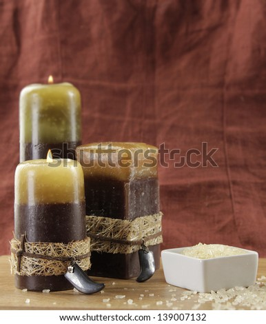 Spa still life with candles and vanilla bath salt om brown background