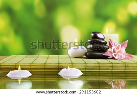Spa still life with flowers and candlelight on green blurred background - stock photo