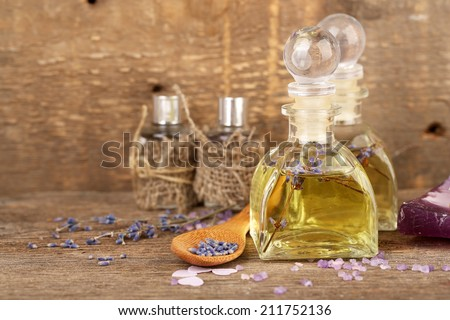 Spa still life with lavender oil and flowers on wooden table - stock photo