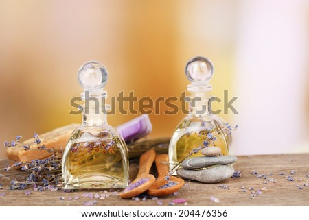 Spa still life with lavender oil and flowers on wooden table, on light background - stock photo