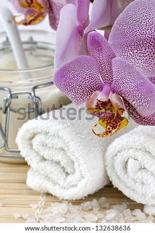 Spa still life with orchid, towel, cream, salt - stock photo
