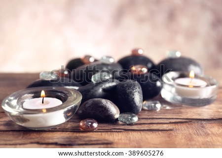Spa still life with stones and candlelight on blurred pastel background - stock photo