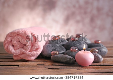 Spa still life with stones, crystals, towel and candlelight on blurred pastel background - stock photo