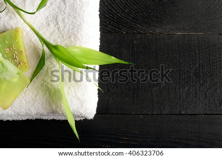 SPA still life with towel and bamboo leaves on a black wooden surface - stock photo
