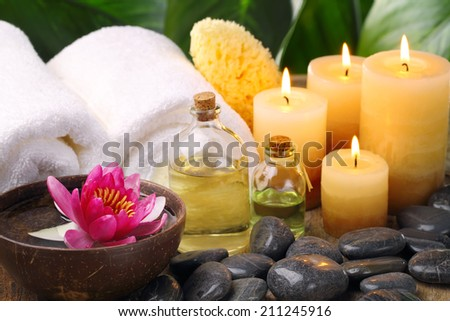 Spa still life with towel,zen stone and burning candles. - stock photo