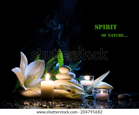 spa still life with white lily, stones and  burning candles on  black bright table with water drop,  on black background  - stock photo