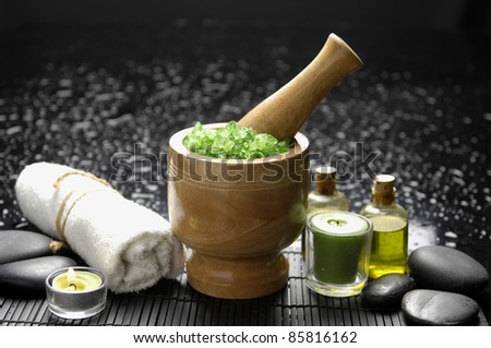 Spa still life wooden mortar and pestle with towel and massage oil - stock photo
