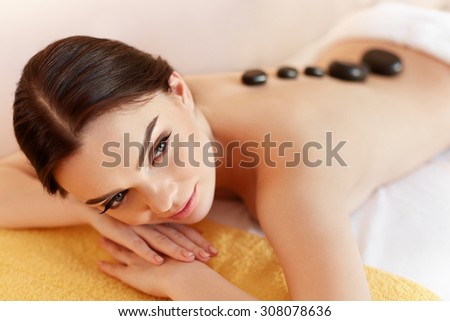 Spa Stone Massage. Young Woman Have Hot Stone Massage Treatments. Spa Hot Stones