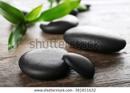 Spa stones and bamboo branch on wooden background - stock photo