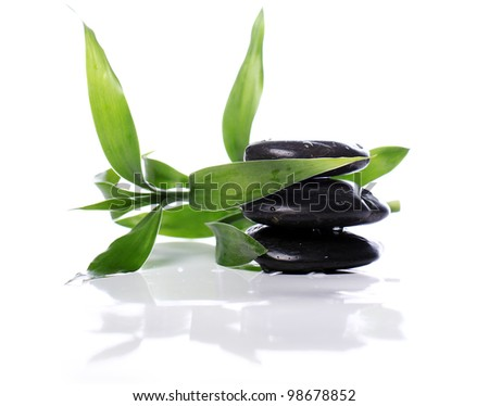 Spa stones and bamboo leaves over white background
