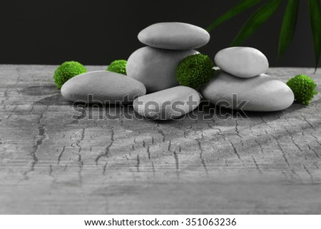 Spa stones and green flower, on dark grey background - stock photo