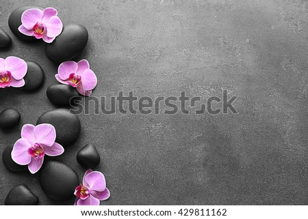 Spa stones and orchids on dark background - stock photo