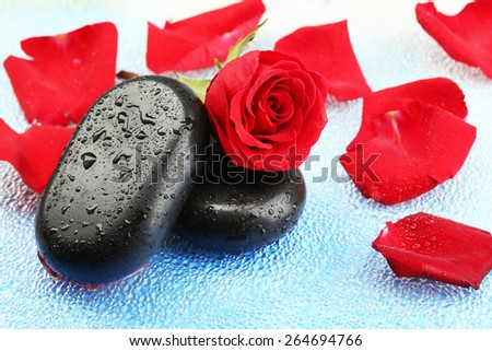 Spa stones and rose petals on colorful background - stock photo