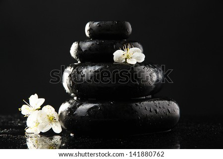 Spa stones and white flowers isolated on black
