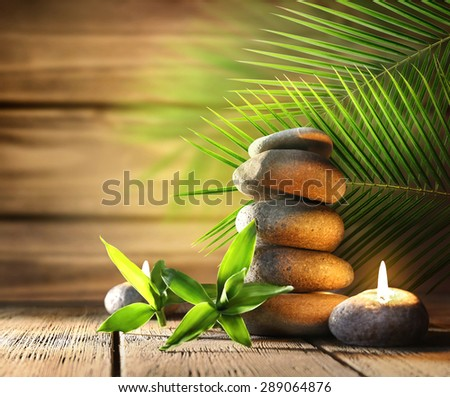 Spa stones, candle on wooden background - stock photo