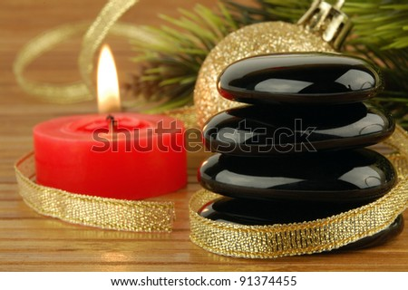 Spa stones, christmas ball and candle with golden ribbon. Focus on a stones. - stock photo