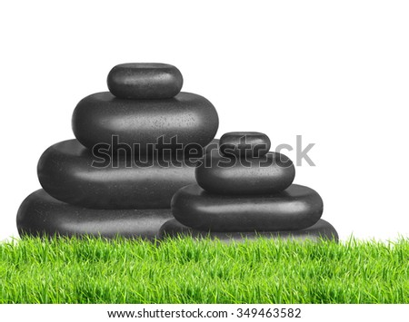 Spa stones in green grass isolated on white background - stock photo