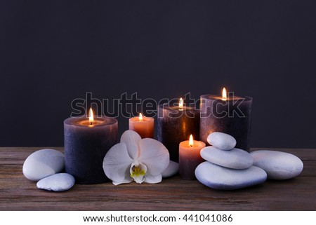 Spa stones with burning candles and flower on grey background - stock photo