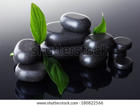 Spa stones with drops and green leaves on grey background - stock photo