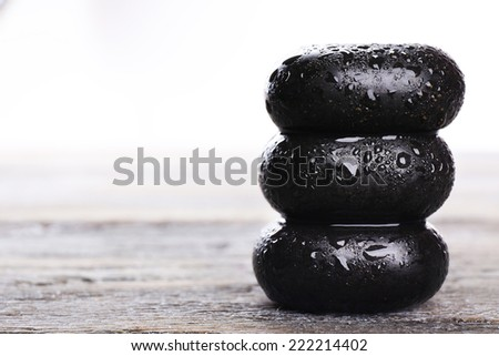 Spa stones with drops on table on light background - stock photo