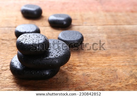 Spa stones with drops on wooden background - stock photo