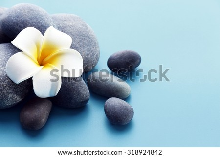 Spa stones with flower on blue background