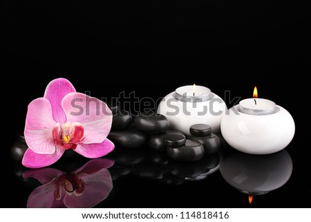 Spa stones with orchid flower and candles isolated on black - stock photo