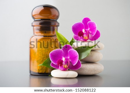 Spa stones with pink orchid and sea salt, on glossy yellow background.