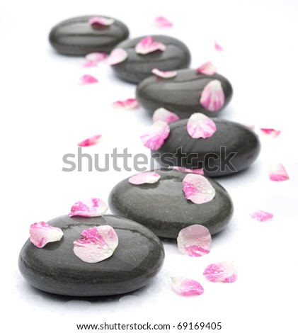 Spa stones with rose petals on white background. - stock photo