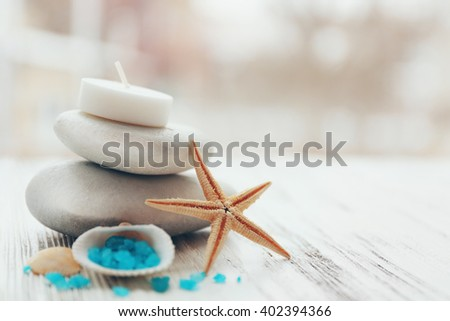Spa stones with starfish and sea salt on white wooden table - stock photo