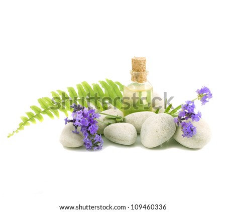 Spa stones with the lavender flowers and a bottle of essential oil - stock photo