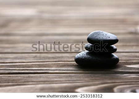 Spa stones with water drops on wooden background - stock photo