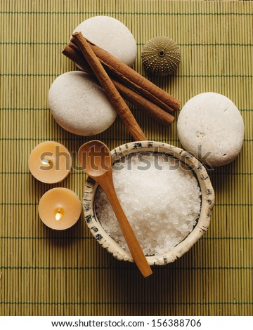 Spa supplies. Sea salt, pebble, cinnamon and candles in a zen spa atmosphere. - stock photo