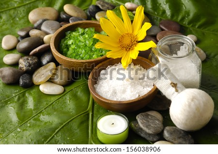 spa supplies with yellow sunflower. salt in bowl ,image of tropical spa. - stock photo
