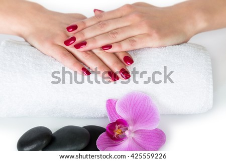 Spa theme portraying pair of female hands with nail polish on towel beside black stones and purple iris flower on white background