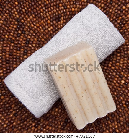 Spa themed image with soap and towel on a dark beaded background. - stock photo
