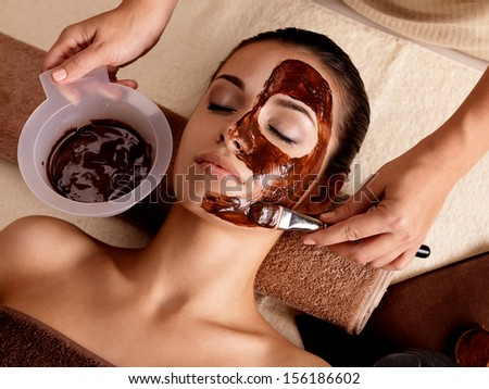 Spa therapy for young woman having  facial mask at beauty salon - indoors - stock photo