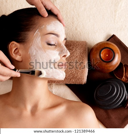 Spa therapy for young woman receiving facial mask at beauty salon - indoors - stock photo
