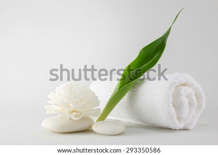 Spa towel decorated with green leave handmade, flower and white stone - stock photo