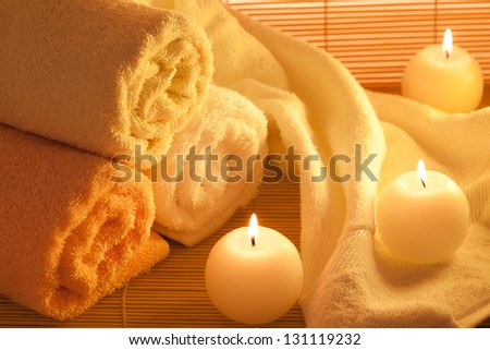 Spa towels and candle on bamboo background. - stock photo