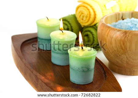 Spa towels with candles isolated on white