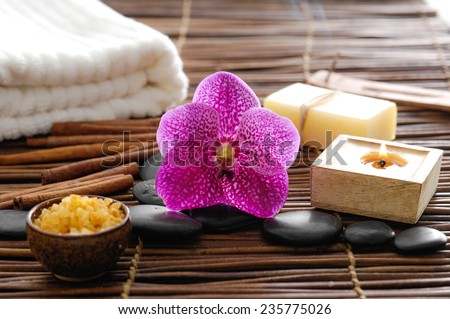 Spa treatment. Burning candle, spa stones, towel , orchid flowers - stock photo