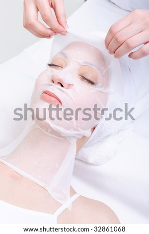 spa treatment for young woman's face in the beauty salon - stock photo