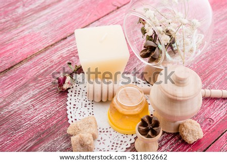 spa treatment -  star anise, honey, salt, arranged with soap bar, pebbles and towels on wood - stock photo