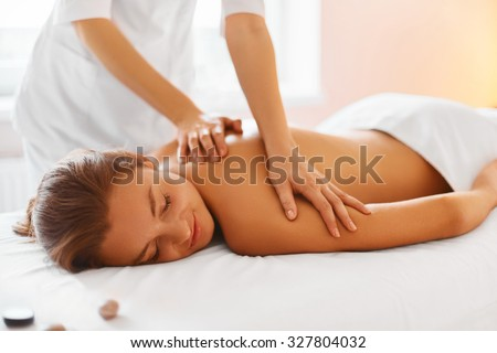 Spa treatment. Woman enjoying relaxing back massage in cosmetology spa centre. Body care, skin care, wellness, wellbeing, beauty treatment concept. - stock photo
