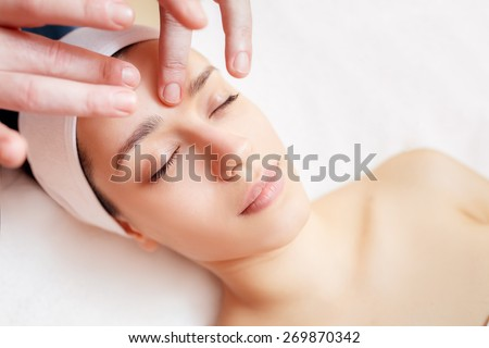 spa treatments. facial massage beautiful girl in a beauty salon - stock photo