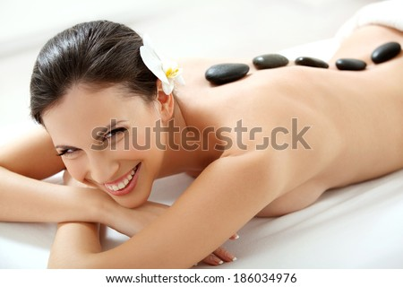 Spa Tretment. Beautiful Woman Getting Spa Hot Stones Massage in Spa Salon. - stock photo